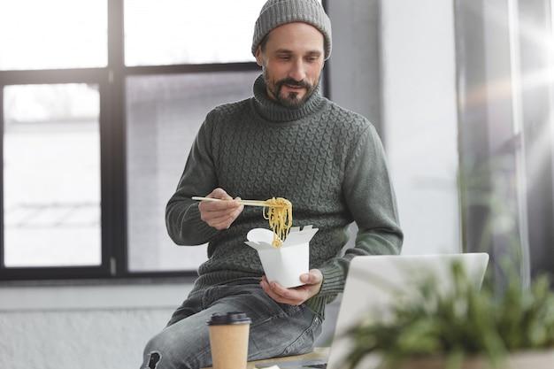 Bebaarde man met gebreide warme trui en muts met lunch