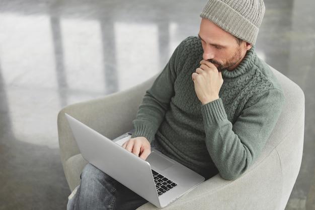 Bebaarde man met gebreide warme trui en muts
