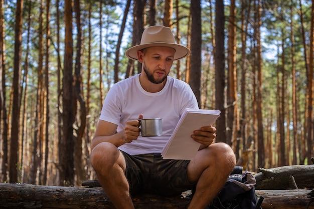 Bebaarde man met hoed houdt een kaart in zijn handen tijdens een wandeling. wandeling in de bergen, bos.
