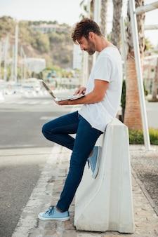 Bebaarde man met jeans met een laptop