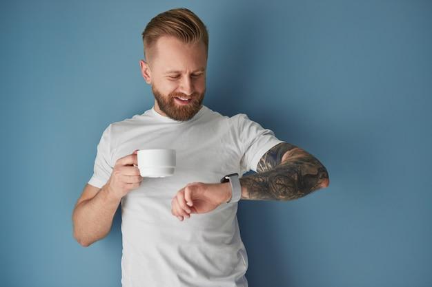 Bebaarde man met koffie die tijd controleert