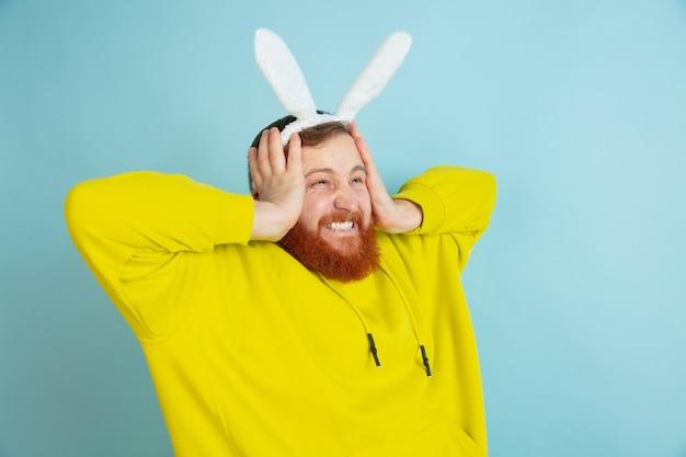 Bebaarde man met konijnenoren voor pasen
