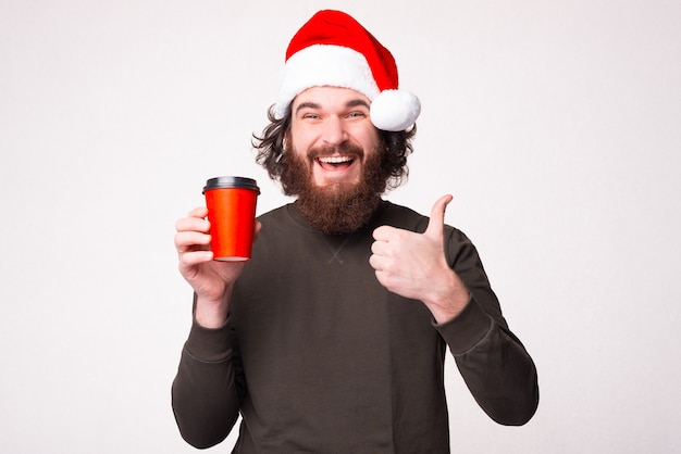 Bebaarde man met kopje koffie te gaan en duim opdagen en het dragen van kerstman hoed