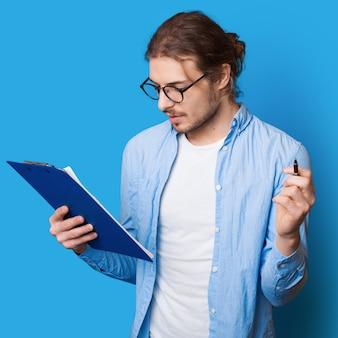 Bebaarde man met lang haar die aantekeningen maakt in een document met een pen en een map op een blauwe studiomuur