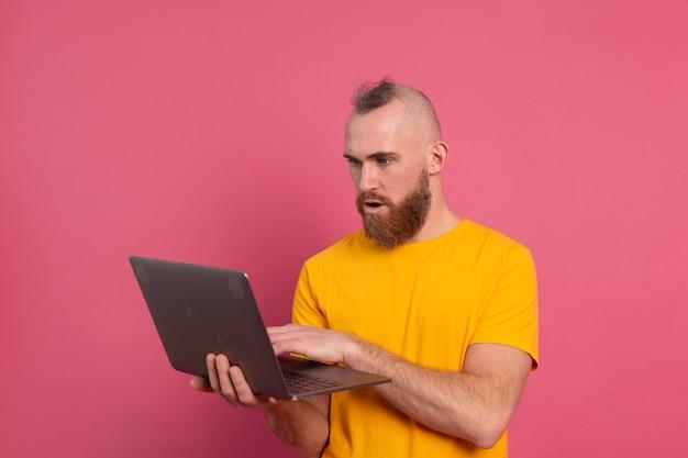 Bebaarde man met laptop geïsoleerde schokemoties op roze achtergrond