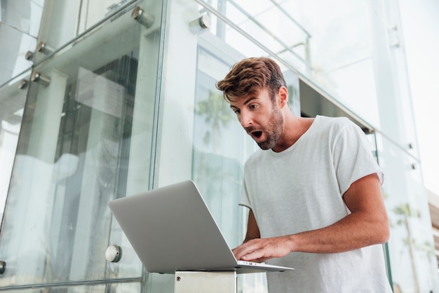 Bebaarde man met laptop verrast
