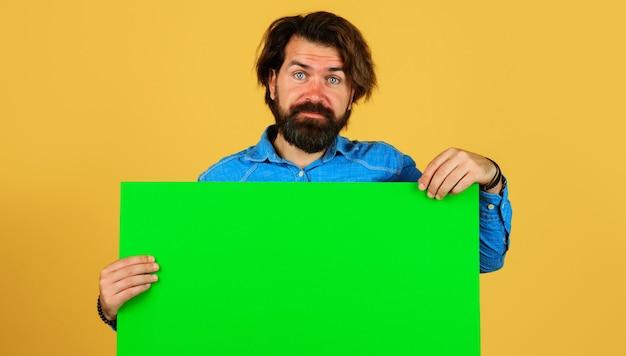 Bebaarde man met leeg bord. glimlachend mannetje met reclamebanner. ruimte voor tekst. zwarte vrijdag. verkoop en korting.