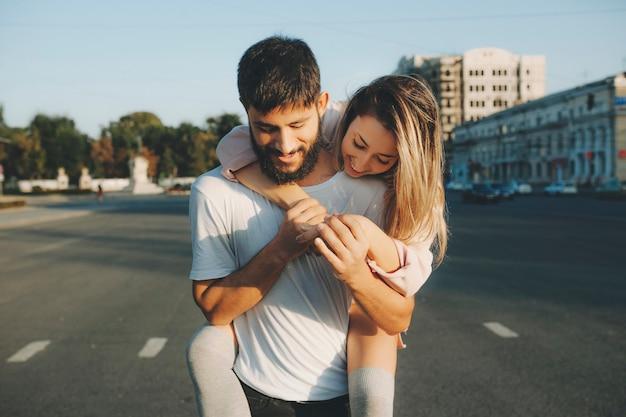 Bebaarde man met meisje meeliften permanent op straat in zonlicht en gelukkig lachend