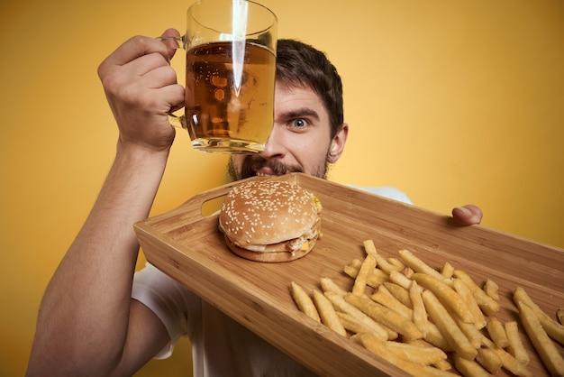 Bebaarde man met mok bier en fastfood