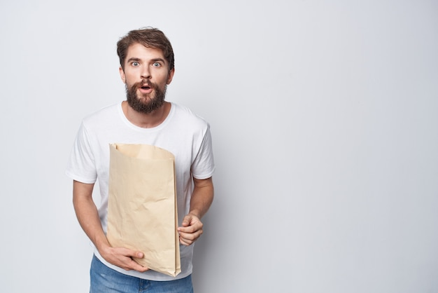 Bebaarde man met papieren zak in witte tshirt winkel mockup