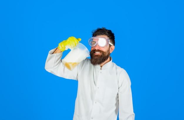 Bebaarde man met reinigingsapparatuur bebaarde man met wasmiddel bebaarde man in uniform en rubber