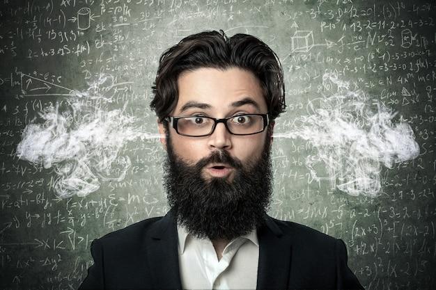 Bebaarde man met rook die uit zijn oren komt, over bord met wetenschappelijke formules en berekeningen in natuurkunde en wiskunde, concept vermoeide student of jonge leraar