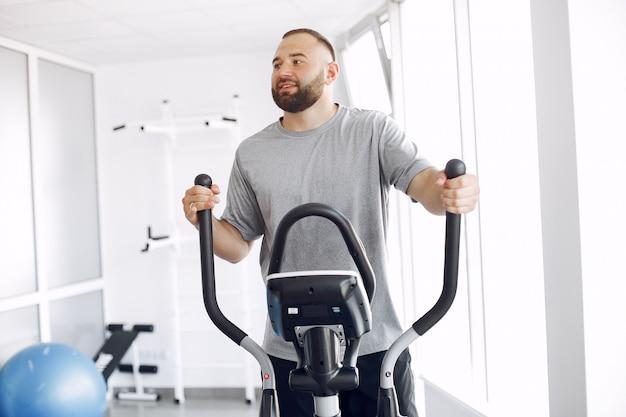 Bebaarde man met spin-fiets in fysiotherapie kamer