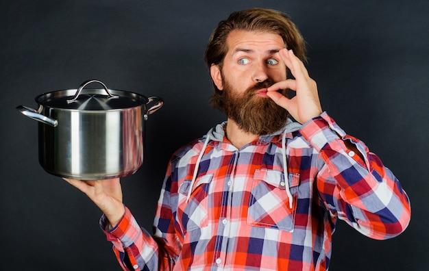 Bebaarde man met steelpan toont teken ok. koken eten, voorbereiding, keuken. restaurant keuken.