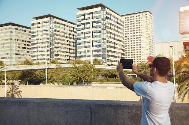 Bebaarde man met tatoeages die een foto neemt van stadsgebouwen en bomen