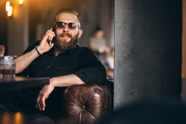 Bebaarde man met telefoon zit in een café