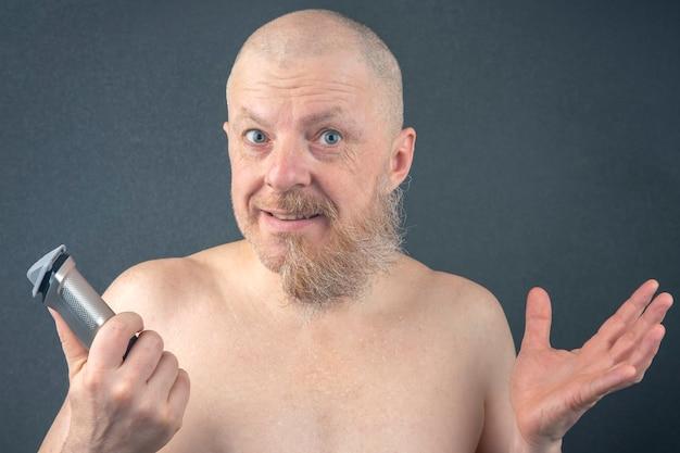 Bebaarde man met trimmer om baard in de hand aan te passen. grooming en modieuze kapperszaak. baardlengte correctie