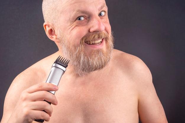 Bebaarde man met trimmer om baard in de hand aan te passen