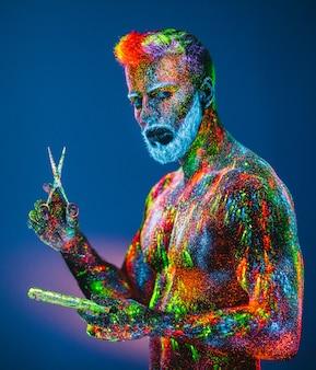 Bebaarde man met ultraviolet poeder in een herenkapper