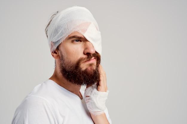 Bebaarde man met verbonden hoofd en oog ziekenhuisopname lichte achtergrond