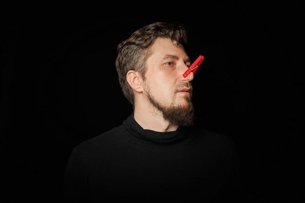 Bebaarde man met wasknijper op neus. slechte stank, grappige grappenmaker, grapconcept. lach om jezelf. rode wasknijper - symbool van zelfspot en een grapje. zwarte achtergrond.