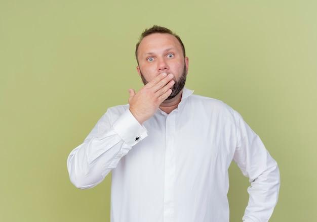 Bebaarde man met wit overhemd dat mond bedekt met hand wordt geschokt staande over lichte muur