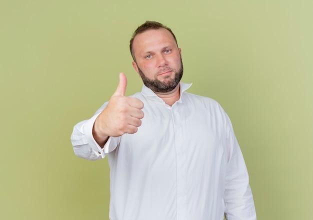 Bebaarde man met wit overhemd duimen opdagen glimlachend zelfverzekerd staande over lichte muur