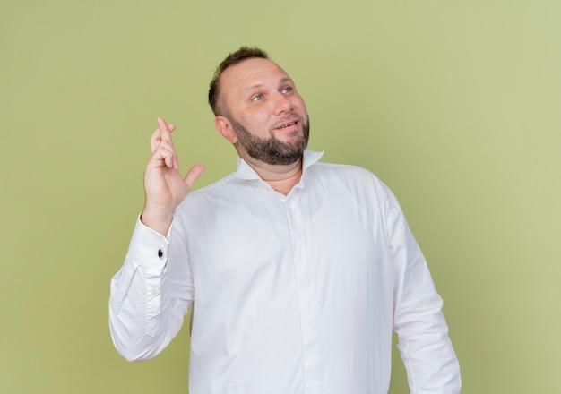 Bebaarde man met wit overhemd kruising vingers opzij kijken wens met hoop expressie staande over lichte muur