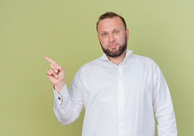 Bebaarde man met wit overhemd met ernstig gezicht wijzend met de vinger naar de zijkant staande over lichte muur
