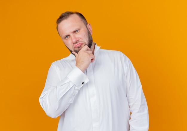 Bebaarde man met wit overhemd met hand op kin denken staande over oranje muur