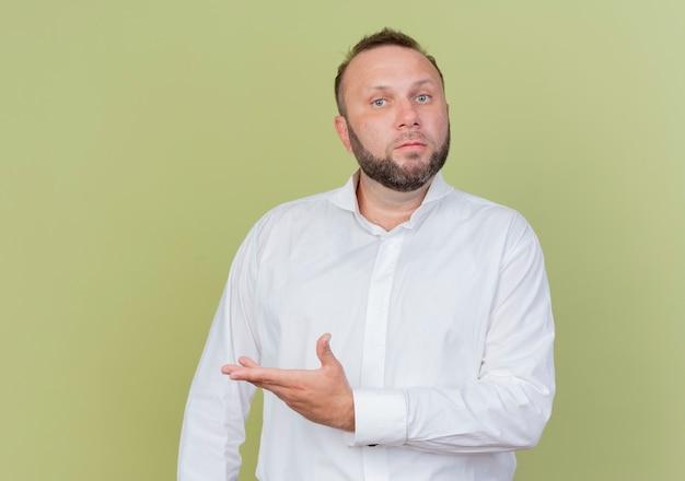 Bebaarde man met wit overhemd wijzend met arm naar de zijkant verward staande boven lichte muur