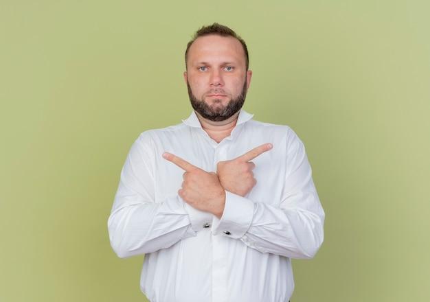 Bebaarde man met wit overhemd wijzend met wijsvingers in tegengestelde richtingen staande over lichte muur