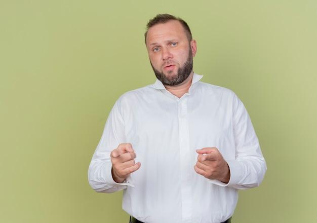 Bebaarde man met wit overhemd wijzend met wijsvingers op zoek verward staande over lichte muur