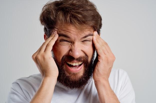 Bebaarde man met zijn hoofdpijn stress emoties geïsoleerde achtergrond