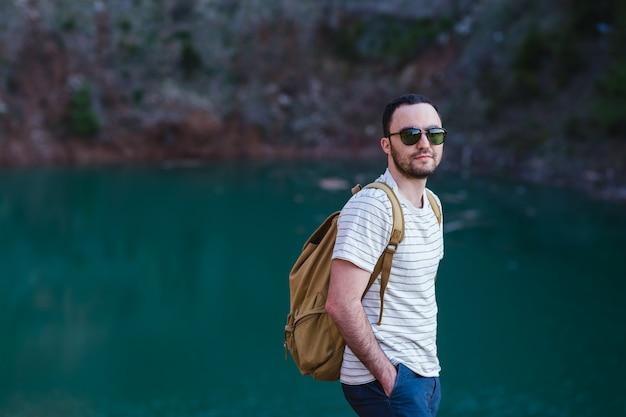 Bebaarde man model vormt naast een groen water meer.