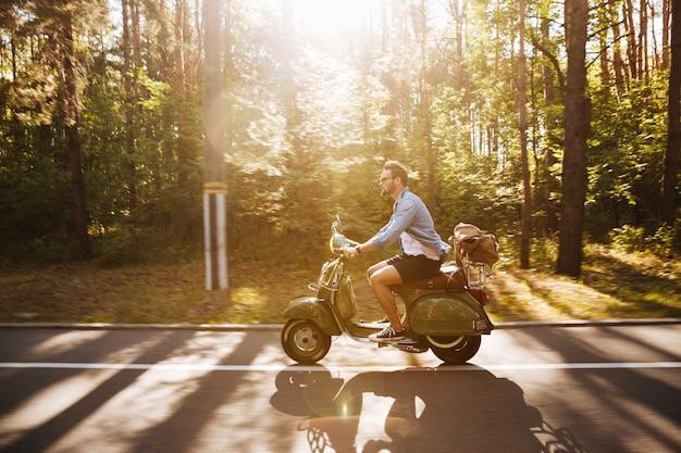 Bebaarde man op scooter buitenshuis. opzij kijken.