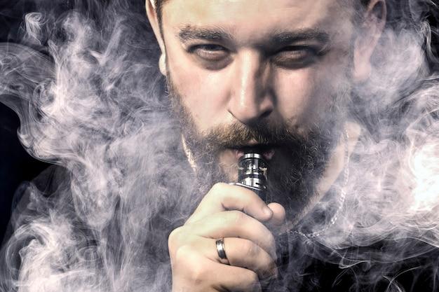 Bebaarde man op zwarte muur close-up met vape in mond omgeven door rook