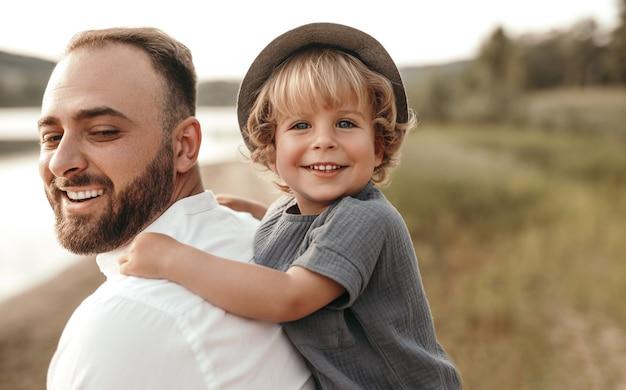 Bebaarde man piggyback rit geven aan schattige blonde jongen