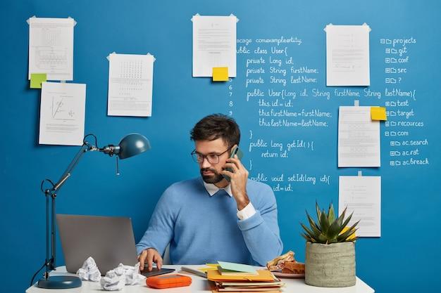 Bebaarde man praat over het initialiseren van database-informatie, gericht op laptop, draagt een bril voor zichtbescherming, controleert de toepassing, zit op het bureaublad.