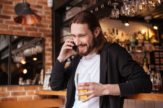 Bebaarde man praten over telefoon met kopje bier