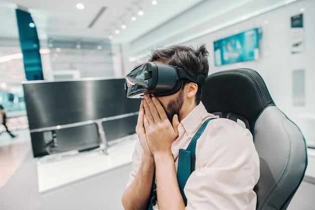 Bebaarde man probeert virtual reality-technologie zittend in een stoel in tech store.