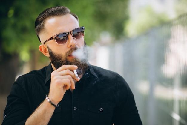 Bebaarde man rokende sigaret