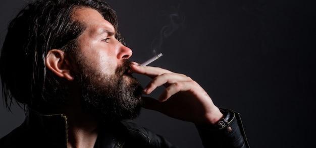 Bebaarde man rook sigaret. modieuze man in leren jas met sigaret. rokende hipster.