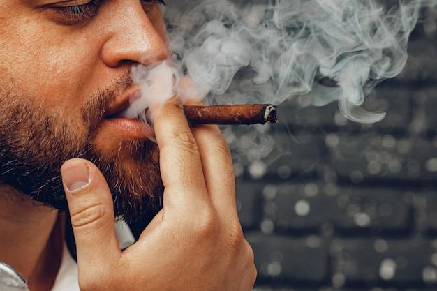 Bebaarde man rookvrije sigaar tegen zwarte bakstenen muur