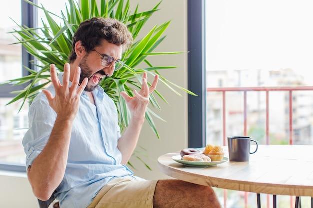 Bebaarde man schreeuwen met de handen in de lucht, woedend, gefrustreerd, gestrest en boos