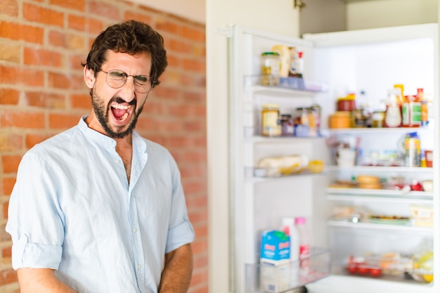 Bebaarde man schreeuwt agressief, kijkt erg boos, gefrustreerd, verontwaardigd of geïrriteerd, schreeuwt nee