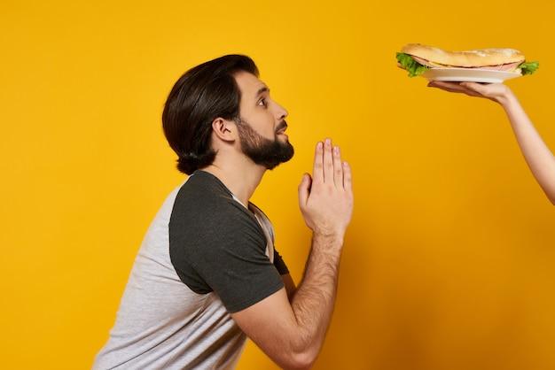 Bebaarde man smeekt om sandwich te eten. vleeseters.