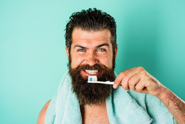 Bebaarde man tandenpoetsen met tandenborstel en tandpasta. mondhygiëne. ochtend behandelingen.