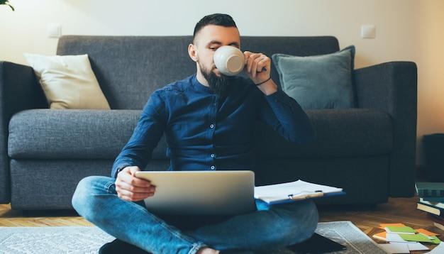 Bebaarde man thuis werken op de vloer met een computer en documenten terwijl hij een kopje koffie drinkt