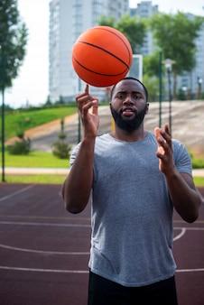 Bebaarde man toont een truc met een bal